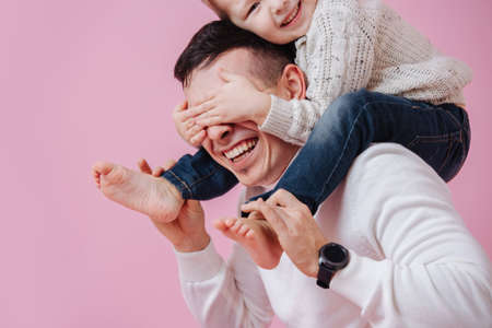 Loving son sitting on dads shoulders, covering his eyes. Over dark pink