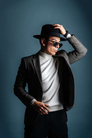 Essentric man in a jacket, sunglasses and classical hat over shades of grey Archivio Fotografico