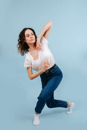 Cute contemporary dancer crossing her legs in a lunge forward