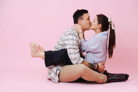 Young couple sitting on floor, hugs and kissing on a pink background