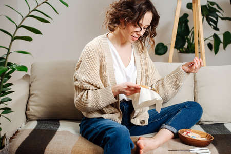 Excited young woman sewing in comforts of her apartment, embroiders a picture
