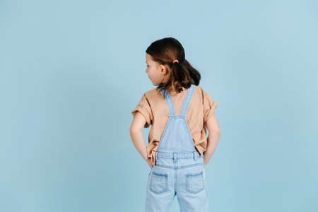 Fashionable little girl posing with her back turned, looking to the side over blue background. She has two ponytails, wears overalls. Hands in pockets. Foto de archivo