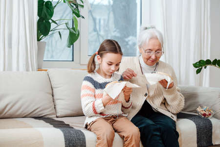 A little girl of seven years and her gray-haired grandmother of seventy years, together are passionate about embroidery.