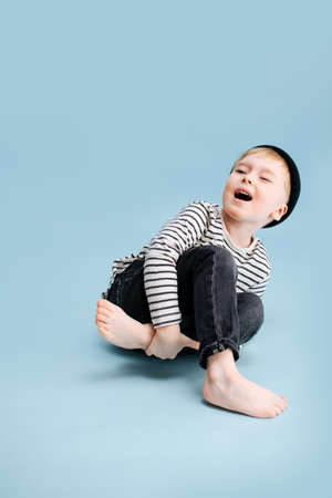 Acting blond boy sitting on the floor, tilting to the side, holding his leg. He's wearing striped long-sleeve shirt and black cap. Studio shot. Over blue background.