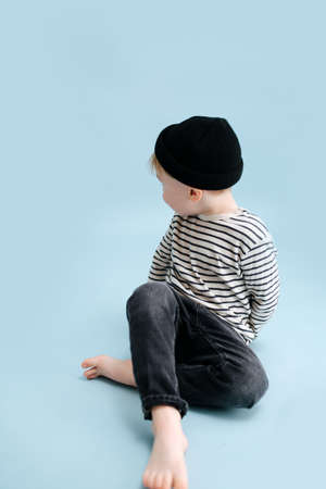 Little blond boy sitting on the floor with legs crossed, looking behind his shoukder. He's wearing striped long-sleeve shirt and black cap. Studio shot. Over blue background.