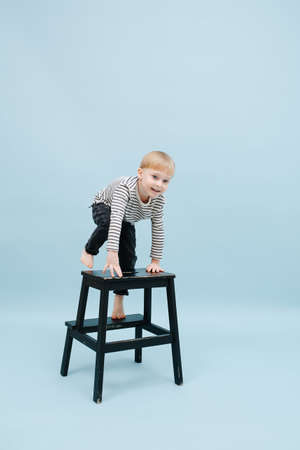 Enthusiastic little barefoot blond boy climbing on a stepping stool. He's wearing striped long-sleeve shirt. Studio shot. Over blue background.