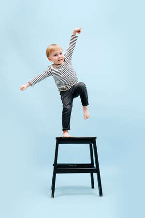 Agile barefoot blond boy balancing on one foot on a stepping stool, tilting to the side. He's wearing striped long-sleeve shirt. Studio shot. Over blue background.