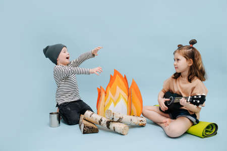 Loud boy and quiet girl with guitar are sitting next to a fake campfire with paper flames and birch logs. They are acting camping scene, getting warm over blue background.