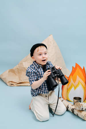 Excited little boy sitting on her knees next to a fake campfire and a paper tent. He is holding binoculars in his hands. Over blue background