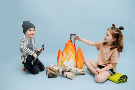 Joyful girl and boy sitting next to a fake campfire with paper flames and birch logs. Over blue background. Boy is playing guitar, girl holding steel mug and telling something.