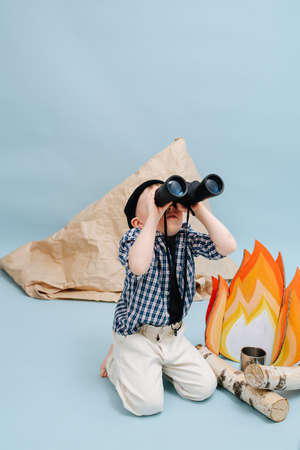 Pretending boy sitting on her knees next to a fake campfire and a paper tent, looking up through binoculars. Over blue background