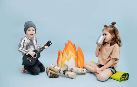 Girl and boy sitting next to a fake campfire with paper flames and birch logs. They are acting scene, getting warm over blue background. Boy is playing guitar, girl is drinking from a steel mug.