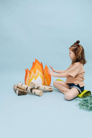 Subtly smiling little girl sitting next to a fake campfire with paper flames and birch logs. She's acting scene, getting warm over blue background