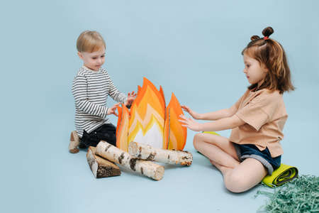 Playing girl and boy sitting next to a fake campfire with paper flames and birch logs. They are acting scene, getting warm over blue background