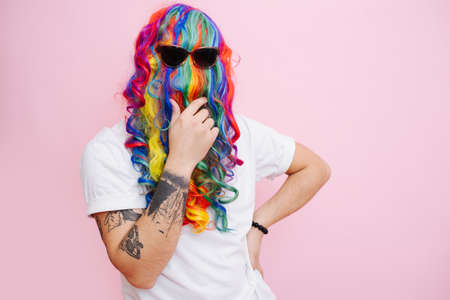 Hilarious looking man in a wig over face, worn back to front and sunglasses over it. He is stroking beard resembling hair. Over pink background.