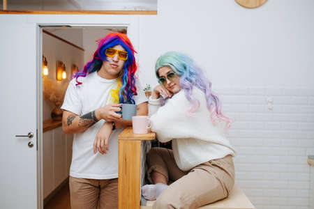Silly looking couple in colorful wigs and sunglasses drinking tea in a kitchen. She's sitting on a table, he's standing right next to her. Stock fotó