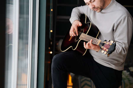 Handsome middle aged man playing guitar in a bedroom next to a window, enjoying himself. He's wearing comfortable clothes.
