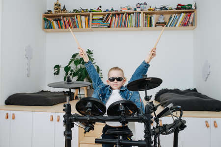 Little boy superstar in sunglasses playing electronic drums at home. He is wearing jeans jacket, lifting his drumsticks up, imaging himself to be a popular musical performer. Frontal view. Stock Photo