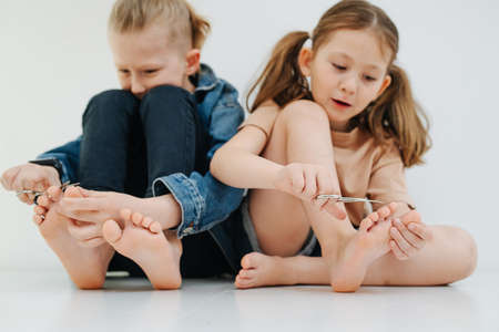 Funny kids. Little siblings with feet clipping nails on their toes. Reklamní fotografie