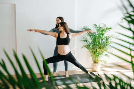 Yoga instructor helping pregnant woman to do warrior asana, adjusting angle of arms. Woman is standing on a mat in a big studio, lunging to side. She's wearing black top and pants
