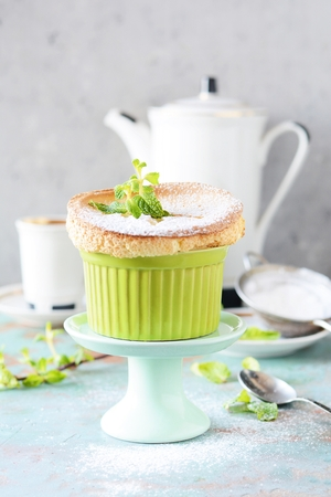 Delicious vanilla souffl in icing sugar, hot coffee and fresh mint. Delicious French dessert to the coffee table.
