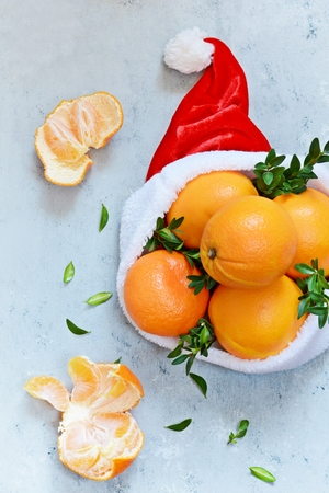 Ripe oranges with hat on the blue background. Festive mood, Christmas and New Year 免版税图像