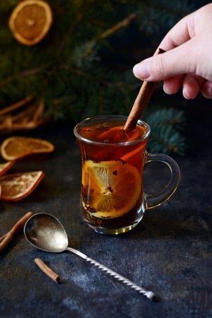 Christmas tea with orange and spices. Selective focus. Hot spicy tea on tray with branches of coniferous tree. Christmas concept on dark wooden background