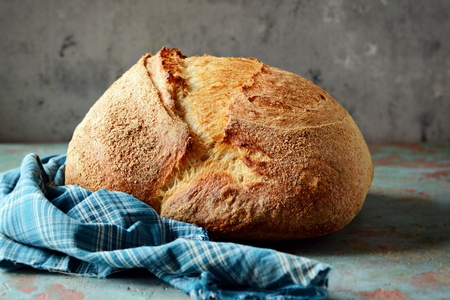 Homemade Freshly Baked Country Bread made from wheat and whole grain flour on a gray-blue background. French bread Stock Photo
