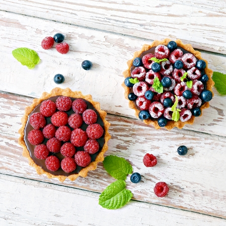 Raspberry and blueberry tartlets with mint leaves, selective focus. Fresh fruit tart on white background, freshly homemade fruit cake on a table