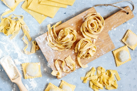 Homemade italian pasta, ravioli, fettuccine, tagliatelle. The cooking process, raw pasta. Tasty raw ravioli with ricotta and spinach, with flour on background