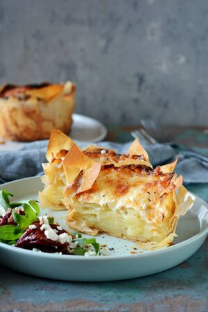 Potato gratin baked in filo dough, with crispy cheese crust and with a salad of arugula, sun-dried tomatoes and cheese on a blue background. A dish of french cuisine Stock Photo