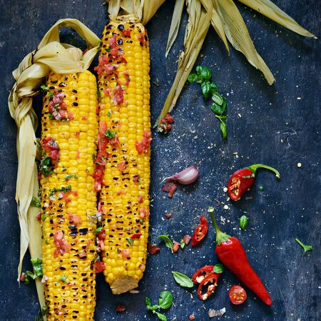Grilled sweet corn with tomato salsa, cilantro, basil, chili pepper and garlic. Mexican food. Top view. Copy space. Summer vegan dinner or snack.