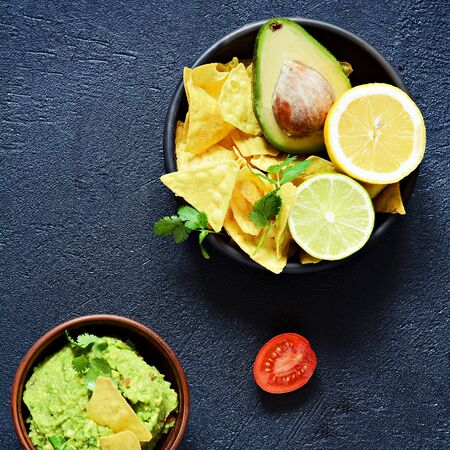 Bowl of guacamole dip with corn nachos (chips) and ingredients on a black background, selective focus. Mexican national dish.