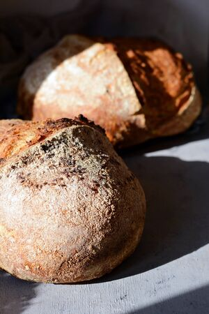 Homemade Freshly Baked Country Bread made from wheat and whole grain flour on a gray-blue background. French Freshly baked bread. Slicing homemade bread