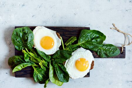 Fried eggs for breakfast with fresh spinach on rye bread toast. Hearty tasty breakfast on a blackboard on a blue background.