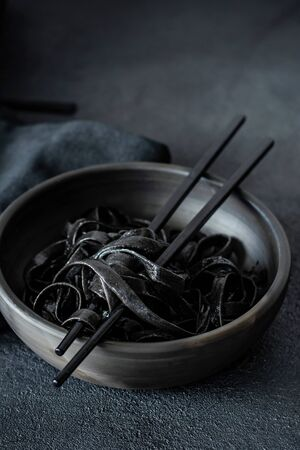 Black pasta with cuttlefish ink in a black plate on a black background. Rare Italian Seafood Pastes.