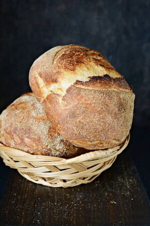 Homemade Freshly Baked Country Bread made from wheat and whole grain flour on a dark background. French Freshly baked bread. Slicing homemade bread