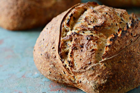 Homemade Freshly Baked Country Bread made from wheat and whole grain flour on a dark background. French Freshly baked bread.