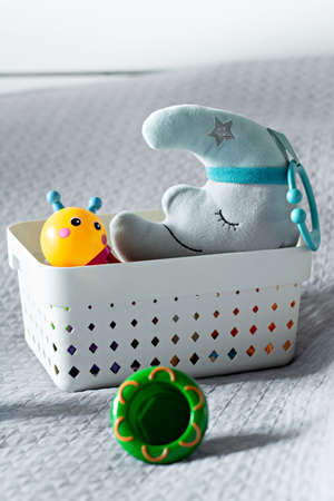 Basket with children's toys on the bed in the bedroom on a gray bedspread. Toys for a child, a moon and a color caterpillar.