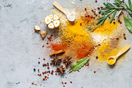 Various spice powders (paprika, curry, coriander, ginger, dried onions and garlic, turmeric, cinnamon, pepper, anise) and herbs (rosemary, bay leaf) on gray background. Indian and Asian cuisine.