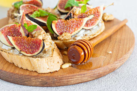 Crispy bruschetta with soft ricotta, ripe figs, walnuts and pine nuts, mint and honey on a light background. Figs fruit toast on a wooden board with honey and walnut.