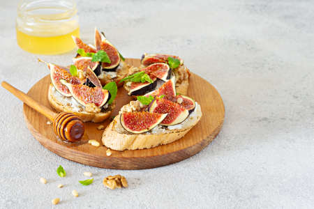 Crispy bruschetta (toast) with soft ricotta, ripe figs, walnuts and pine nuts, mint and honey on a light background. Figs fruit toast on a wooden board with honey and walnut.