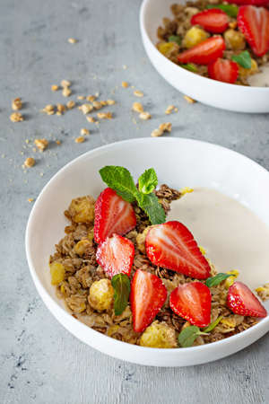 Homemade crunchy granola with nuts, dried fruits, fresh strawberries, mint and yogurt (fermented baked milk) on a white plate on gray background. Healthy breakfast concept.
