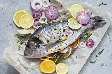 Fresh fish dorado. Raw dorado with herbs, spices and lemon and lime slices ready to cook on a gray background. Top view. Fresh fish gilt-head bream with salt, herbs and pepper.