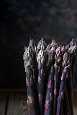 Fresh bunch of purple asparagus on a dark wooden background.