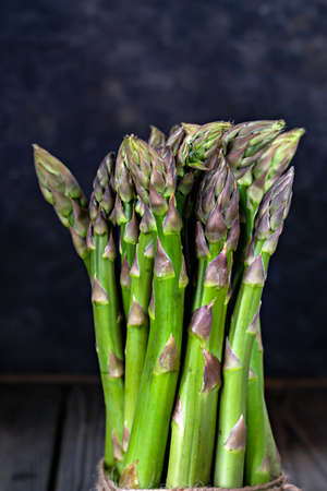 Green asparagus on a dark wooden background. Raw food concept, place for copy space.