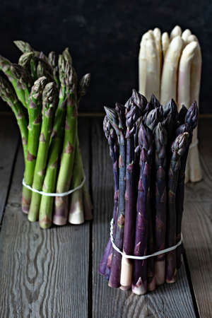 Raw white, purple, green asparagus on a dark wooden background. Zdjęcie Seryjne