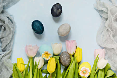 Bouquet of tulips with easter eggs on a light blue background. Happy Easter, spring flowers.
