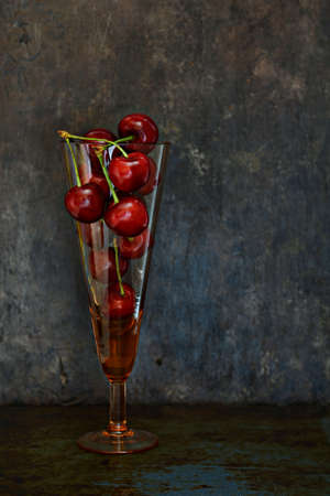 Ripe cherry in a glass on a dark background. Fruit composition. Food art, copy space.