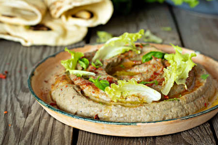 An oriental dish of baked eggplant babaganush (eggplant puree) with spices, herbs, lettuce and oriental flatbreads on wooden background.